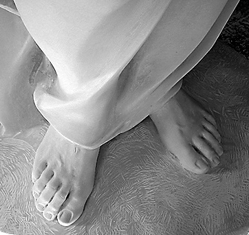 Feet closeup (detail) in sculpture in white Carrara marble.