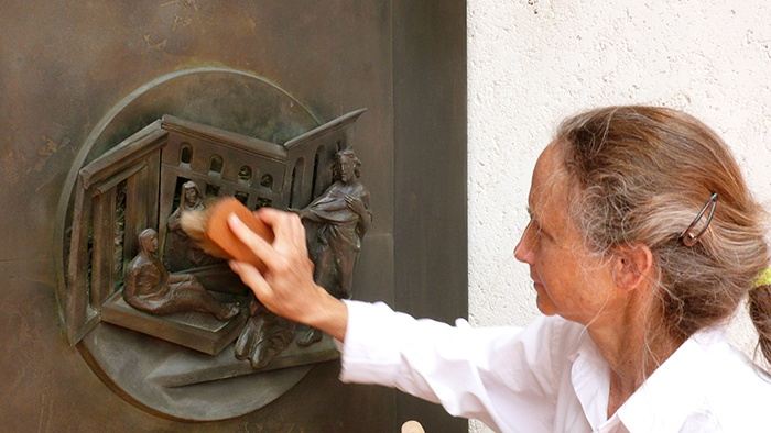 Artist Jill Burkee polishing roundel on bronze portal