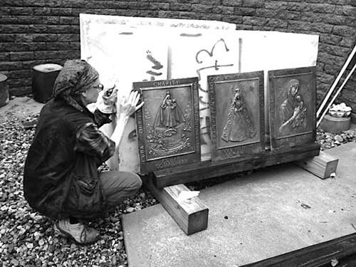 Jill Burkee checking her patina on bronze reliefs